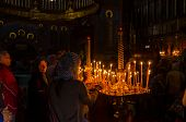 POCHAYIV, UKRAINE - AUGUST 14: Unidentified orthodox believers light candles in Holy Dormition Pocha