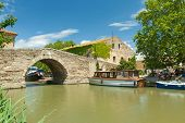 LE SOMAIL, FRANCE - JUNE 22: Boat at bridge at Le Somail on June 22, 2013 on the Canal du Midi, Fran