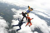 image of sky diving  - Four skydivers jump from a plane with clouds in the background - JPG