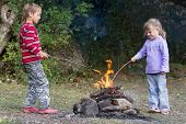 two children boy and girl playing with fire on natural background