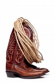 A Pair Of Brown Cowboy Boots And A Coil Of Rope