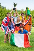 Group of international sports fans, each dressed in the color of their country and carrying the thei
