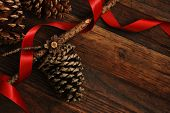 Simple, natural Christmas decor of pine cones with red satin ribbon on rustic, dark wood background.