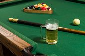 stock photo of suds  - A mug of light beer on a pool table with pool balls and a pool cue.  The beer has suds on top.