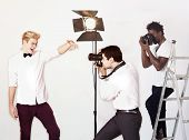 Paparazzi taking photographs of male actor over white background