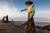 PADANG - AUGUST 25: A fisherman commanders his mates mending the nets for the next cast at sea in Pa