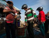 PADANG - AUGUST 25: Fishmongers carry a basketful of fish after a wholesale purchase at a village ma