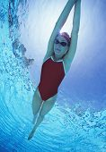 Full length of female swimmer in United States with arms raised swimsuit swimming in pool