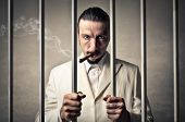 stock photo of mafia  - gangster locked up in a prison smokes cigar - JPG
