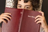 image of bible story  - Young Hispanic child reading and studing the Holy Bible at home - JPG