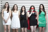 foto of police lineup  - Young woman in superhero costume with friends in a police lineup - JPG