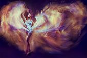 foto of waving  - Woman in waving dress as a flame dancing with flying fabric - JPG