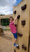 Young boy scaling climbing wall