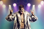 pic of insole  - Portrait of young man in fur coat making rebellious hand gestures in rock concert - JPG