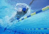 Young professional male athlete doing backstroke in swimming pool