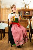 picture of stein  - Young woman in traditional Bavarian Tracht in restaurant or pub with beer and steins and pretzel - JPG