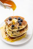 Big Pile of American Blueberry Pancakes with Berries and Maple Syrup