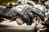 Human hand in a Motorcycle Racing Gloves holds a motorcycle throttle control. Hand protection from falls and accidents.