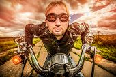 Funny Biker in sunglasses and leather jacket racing on the road (fisheye lens). Filter applied in po