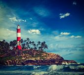 Vintage retro hipster style travel image of old lighthouse and waves of  sea. Kovalam (Vizhinjam) Kerala, India