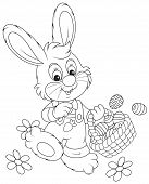 stock photo of cony  - Little rabbit walking with a basket of decorated Easter eggs - JPG