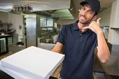 Pizza delivery man holding pizza boxes making a phone gesture in a commercial kitchen