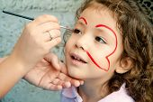 stock photo of face painting  - Little Girl Getting Her Face Painted By An Artist At A Festival