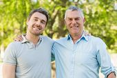 Portrait of a smiling father with adult son at the park