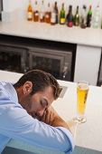 Drunk businessman sleeping beside glass of beer at the local bar