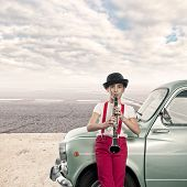 little girl playing clarinet in an old car