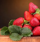 Strawberries with leaves on wooden table on brown  background