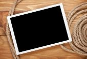 Blank photo frame with ship rope over wooden background