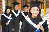 Beautiful  College Graduate Holding Diploma With Classmates
