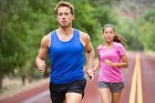 Running couple jogging on road. Runners training for marathon run sprinting. Active young multiracial couple in active healthy lifestyle concept. Asian woman and fit caucasian man fitness model.