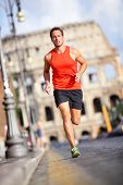 Runner - man running by Colosseum, Rome, Italy. Male athlete training for marathon jogging in city o