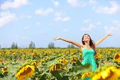 Happy carefree summer girl in sunflower field in spring. Cheerful multiracial Asian Caucasian young