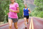 Marathon running athletes couple training on road. Fitness runners, man and woman jogging in active lifestyle.