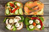 picture of avocado  - Four delicious open wholewheat sandwiches on a wooden picnic table topped with smoked salmon avocado mushrooms cucumber baby spinach and mozzarella cheese - JPG