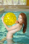 image of poka dot  - young Woman With Yellow Beach Ball Having Fun in an indoor swimming pool - JPG