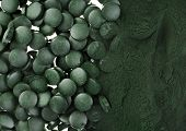 Spirulina powder and tablets algae nutritional supplement heap surface close up top view,  background