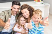 Happy parents giving thumbs up with their young children at home in kitchen