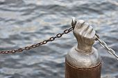 Steel Hand Holding Chain Against The Water
