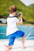 Cute teenage boy with camera enjoying sailing on a luxury catamaran or yacht
