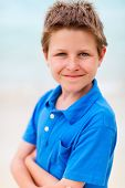 Nine years old boy wearing blue t-shirt outdoors on summer