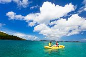 Mother and son paddling on colorful yellow kayaks at tropical ocean water during summer vacation