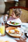 Cute little boy enjoying lunch at restaurant