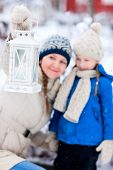 Family of mother and her adorable little daughter with Christmas lantern outdoors on beautiful winte