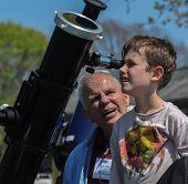 Child Looking Through Telescope with Senior Man