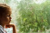 Adorable toddler girl looking at raindrops on the window