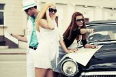 Young fashion people with a road map at the retro car